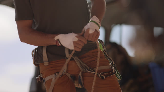 young man looks up as he feeds out rope while preparing for rock climbing expedition. - seil stock-videos und b-roll-filmmaterial