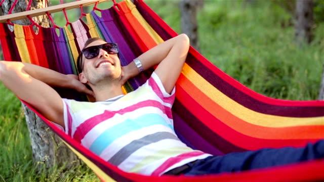 vídeos de stock e filmes b-roll de jovem deitado no balanço em natureza - sunbathing