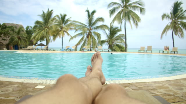 pov young man lying on a deck chair by the swimming pool - deckchair stock videos & royalty-free footage