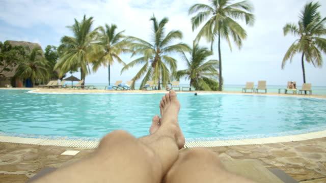 vídeos de stock e filmes b-roll de pov young man lying on a deck chair by the swimming pool - sunbathing