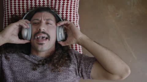 vídeos y material grabado en eventos de stock de young man lying on floor sings along to music with headphones on. - hombres jóvenes