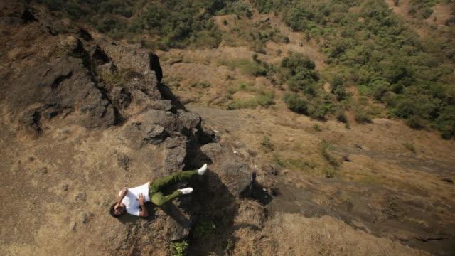 vídeos y material grabado en eventos de stock de young man lying on the rock and talking on the mobile phone  - en el borde