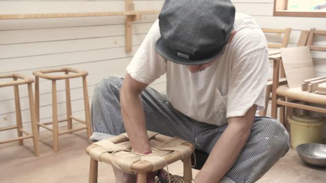 vidéos et rushes de young man make chairs in woodwork studio - seulement des jeunes hommes
