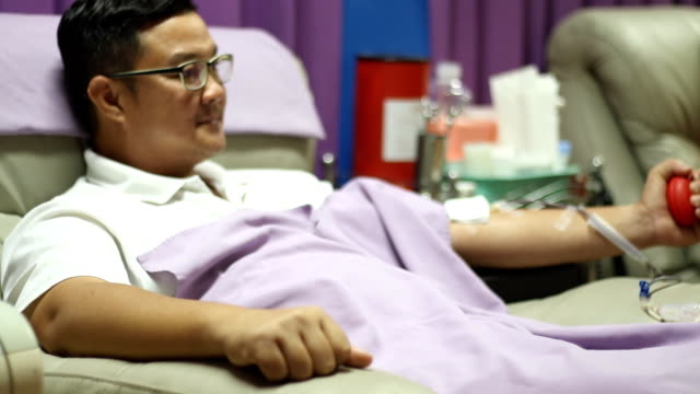 young man make relaxing himself on the sofa during giving blood - donation box stock videos & royalty-free footage
