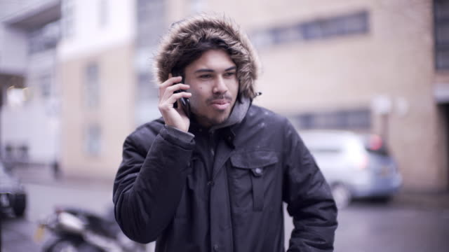 A young man making a phone call in the winter rain