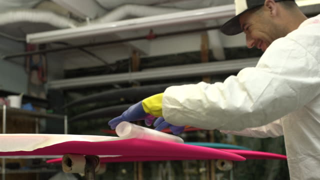 vidéos et rushes de ms young man making a surfboard in his workshop - casquette de baseball