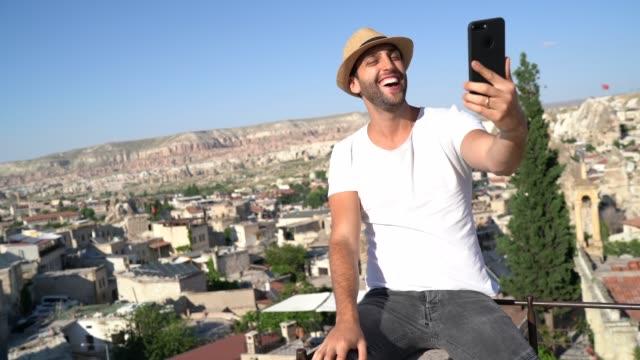 vidéos et rushes de jeune homme faisant un chat vidéo / prenant un selfie à la cappadoce, turquie - blog vidéo