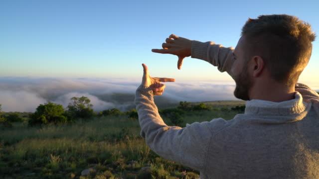 Young man making finger frame on landscape