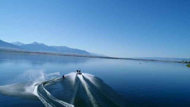 a young man making perfect s-turns while waterskiing behind a boat on a lake - slalom skiing stock videos & royalty-free footage