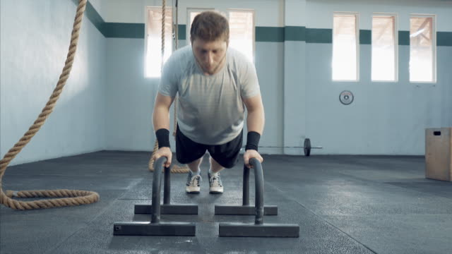 young man making pushups in gym. - cross training stock videos & royalty-free footage