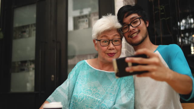 young man making selfie with his grandmother - grandchild stock videos & royalty-free footage