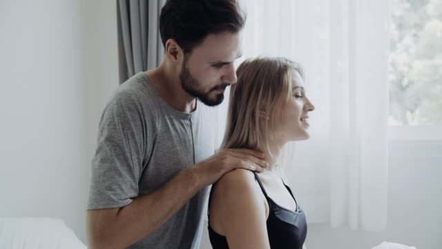young man massaging his wife's shoulder - osteopath stock videos & royalty-free footage