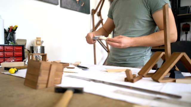 giovane che misura con parti in legno di pinza per il suo progetto artigianale. filmati anonimi. - human face video stock e b–roll