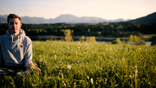 young man meditates in a beautiful nature - meditating stock videos and b-roll footage