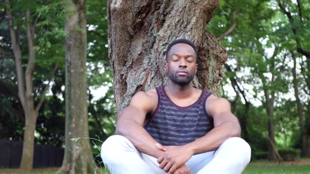 Young man meditating at the park