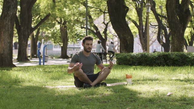 a young man meditating in urban park - general view stock videos & royalty-free footage