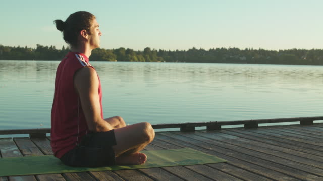 A young man meditating on a dock