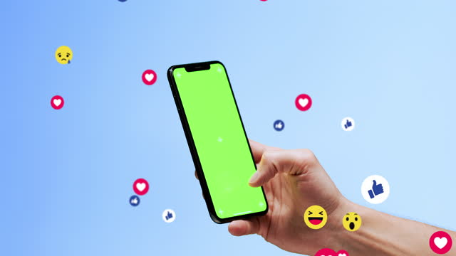 young man messaging on his cellphone, with a chromakey on the screen,  with friends or lover, blue studio background, diverse positive emoji coming out of mobile phone. mobile application for chatting, creative image - following stock videos & royalty-free footage