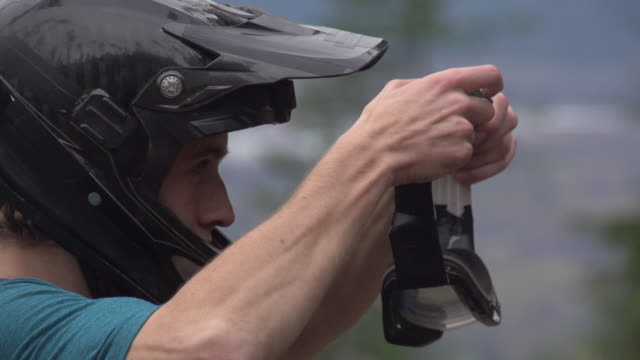 a young man mountain biker putting on goggles. - super slow motion - filmed at 240 fps - solo uomini giovani video stock e b–roll