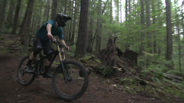 A young man mountain biking in a forest on a mountain.  - Super Slow Motion - filmed at 240 fps