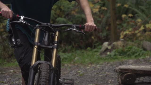 vidéos et rushes de a young man mountain biking in a forest on a mountain.  - super slow motion - filmed at 240 fps - seulement des jeunes hommes
