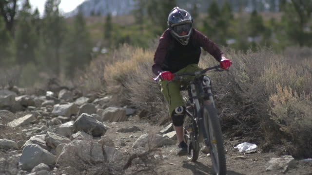 A young man mountain biking on scenic trail in the mountains. - Super Slow Motion - filmed at 240 fps