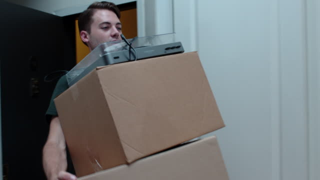 young man moves in cardboard boxes and vinyl record player - package stock videos and b-roll footage