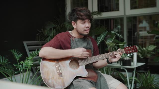 vidéos et rushes de jeune musicien d'homme avec l'appel vidéo sur le smartphone jouant la guitare à la maison - guitariste