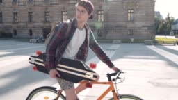 A young man on a bicycle is going to practice skateboarding Good sunny weather and great mood