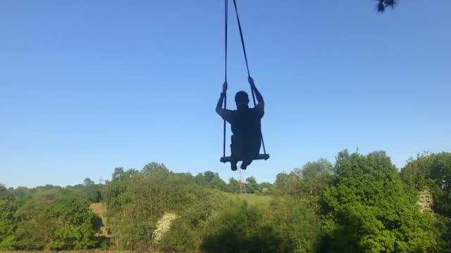 young man on a swing - 屋外遊具点の映像素材/bロール