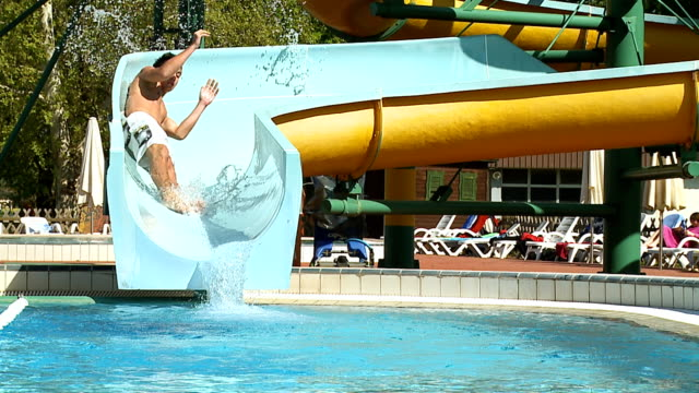 hd slow motion: young man on a winding waterslide - water slide stock videos & royalty-free footage