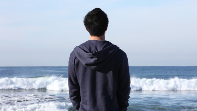 ws young man on beach looking at surfers, back to the camera - standing stock videos & royalty-free footage