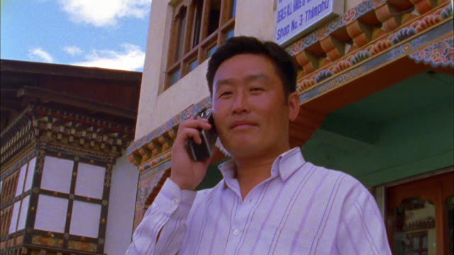 young man on large mobile phone, bhutan available in hd. - 2000年風格 個影片檔及 b 捲影像