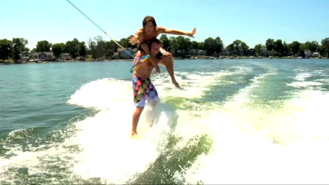 / young man on other man's shoulders as he rides a wake board towed behind a boat SLO MO young men riding wake board behind boat on June 09 2011 in...
