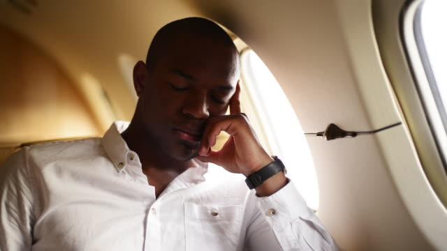 young man on private jet - 腕時計点の映像素材/bロール
