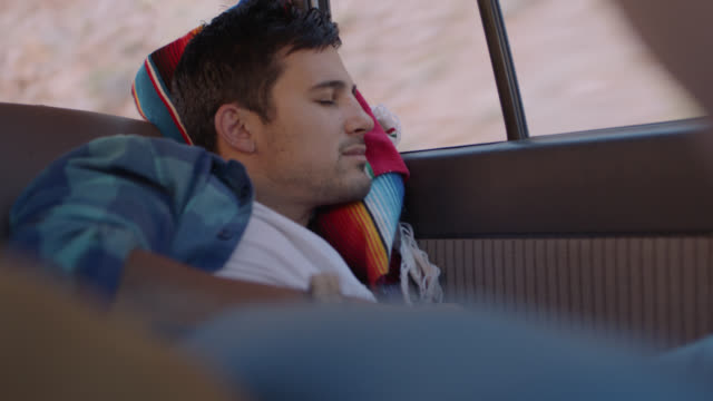 young man on road trip naps in the backseat of car. - schlafen stock-videos und b-roll-filmmaterial