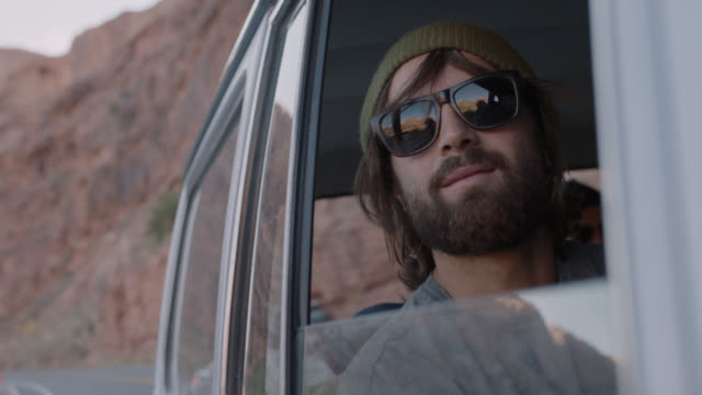 vidéos et rushes de young man on road trip with friends stares out car window at the mountainous terrain. - hipster personne
