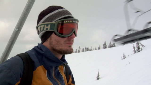 cu, young man on ski lift moving up hill, whitefish, montana, usa - skibrille stock-videos und b-roll-filmmaterial