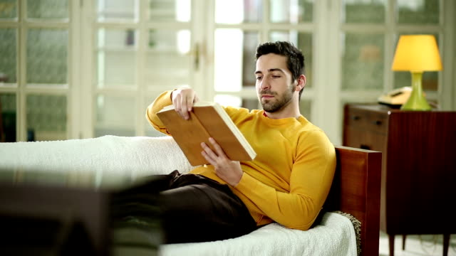 Young man on sofa reading a book