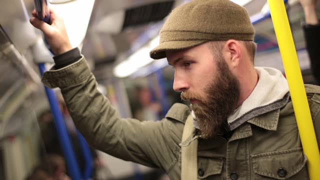 young man on subway train stands clutching the handrail and looks around. - london underground stock videos & royalty-free footage