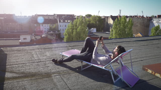 young man on sun lounger using his smartphone - dach stock-videos und b-roll-filmmaterial