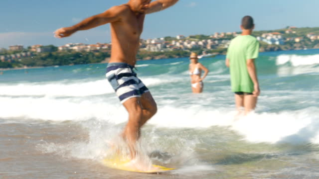 young man on the beach trying to surf a wake board but fails and falls in the water - fallimento video stock e b–roll