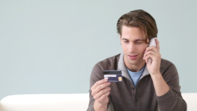 stockvideo's en b-roll-footage met young man on the phone with credit card - draadloze telefoon