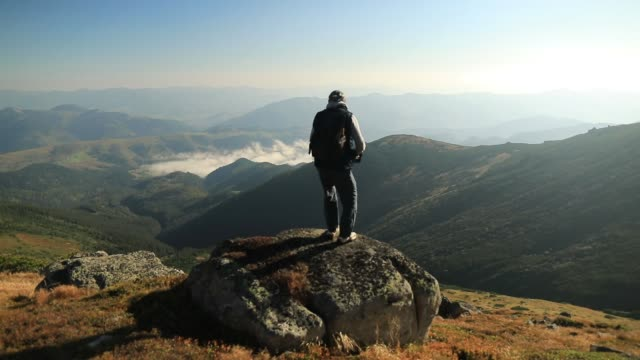 young man on top of a mountain watching the sunset - joy stock videos & royalty-free footage