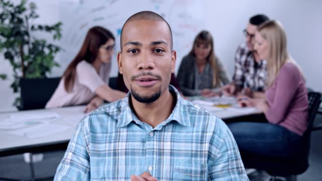 young man on videoconference call during a startup meeting - kommunikationssätt bildbanksvideor och videomaterial från bakom kulisserna