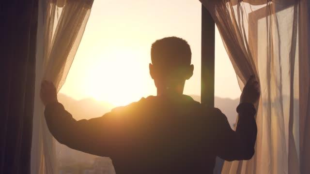 vídeos de stock e filmes b-roll de young man open curtain in the morning - janela aberta