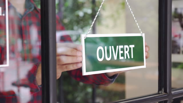 young man opening a french shop - french culture stock videos & royalty-free footage