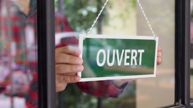 slow-mo: young man opening a french shop - shop sign stock videos & royalty-free footage