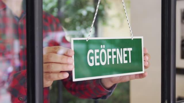 slow-mo: young man opening a german shop - german language stock videos & royalty-free footage