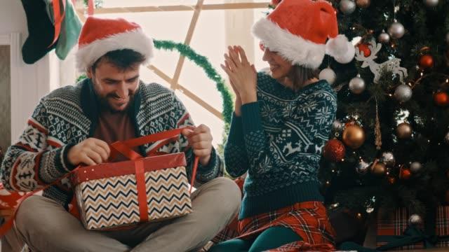 vídeos y material grabado en eventos de stock de joven abriendo su regalo de navidad - regalo de navidad